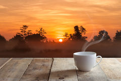 Cup of  coffee over wood table and Sunset Stock Photo
