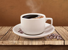 Cup of coffee over wooden table with clipping path. Standing on the wooden table coffee beans and coffee cup Royalty Free Stock Image