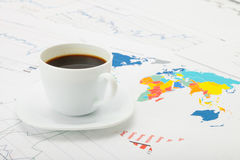 Cup of coffee over world map and financial documents Stock Photography
