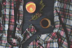 A cup of coffee, pajamas and lighted candle on the wooden background. Cozy home style. Atmospheric picture. Cozy morning in sweet home Stock Image