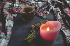 A cup of coffee, pajamas and lighted candle on the wooden background. Cozy home style. Atmospheric picture. Cozy morning in sweet home Royalty Free Stock Photos