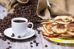 Cup of coffee and pancakes on the table. On the background of coffee beans Royalty Free Stock Image