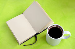 Cup of coffee and paper notebook on green background Royalty Free Stock Photography