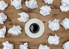 Cup of coffee paper sheets  and crumpled wads on Royalty Free Stock Photography