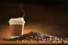 Cup of coffee. Paper cup of coffee with smoke and coffee beans on old wooden background Royalty Free Stock Images