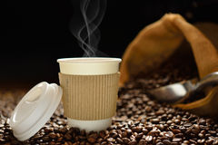 Cup of coffee. Paper cup of coffee with smoke and coffee beans on wooden table Royalty Free Stock Photo
