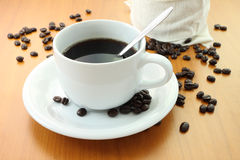 Cup of coffee and part bag beans Stock Photography