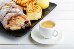 Cup of coffee and pastry on white wooden table Royalty Free Stock Image
