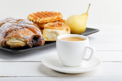 Cup of coffee and pastry on white wooden table Royalty Free Stock Images