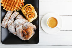 Cup of coffee and pastry on white wooden table. Top view. Royalty Free Stock Photos