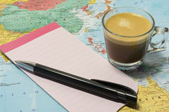 Cup of coffee, pen and notepaper on a map Stock Images