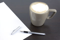 Cup of coffee and a pen on office table. Image royalty free stock photo