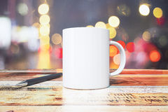 Cup of coffee and pen on a wooden table in cafe at evening Royalty Free Stock Photo
