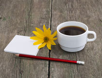 Cup of coffee, pencil with paper and a yellow flower Royalty Free Stock Image