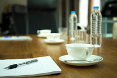 Cup of coffee with pens and paper on wooden table in conference Royalty Free Stock Images