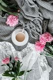 A cup of coffee and peonies on a gray background stock images