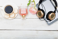 A cup of coffee, perfume and headphones on a white wooden background stock images