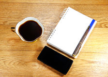 Cup of coffee, a phone and a notepad Royalty Free Stock Images
