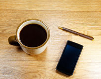Cup of coffee, a phone and a pen Royalty Free Stock Photo