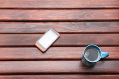 Cup of coffee and the phone on the table Stock Photography
