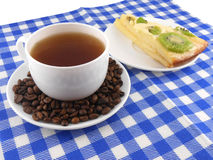 A cup of coffee and a piece of tasty creamy cake with coffee beans Royalty Free Stock Photo
