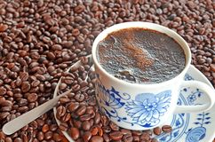Cup of coffee and pile of coffee beans. Porcelain cup of coffee and saucer in pile of brown coffee beans Stock Images