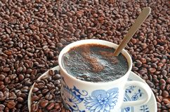 Cup of coffee and pile of coffee beans. Porcelain cup of coffee and saucer in pile of brown coffee beans Stock Photo