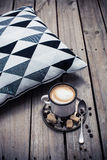 Cup of coffee and pillow on wooden floor Stock Image