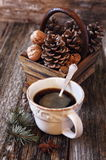 Cup of coffee, pine cones in basket, walnuts and cinnamon sticks Stock Photos