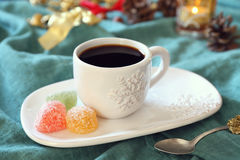 Cup of coffee and pine cones, burning candle and colorful candy Royalty Free Stock Photography
