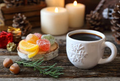 Cup of coffee, pine cones, burning candles and colorful candy Royalty Free Stock Photos