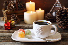 Cup of coffee, pine cones, burning candles and colorful candy Royalty Free Stock Image