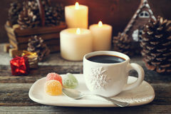 Cup of coffee, pine cones, burning candles and colorful candy Royalty Free Stock Photo