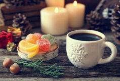 Cup of coffee, pine cones, burning candles and colorful candy Stock Photos