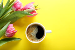 Cup of coffee and pink tulips on yellow background, top view Stock Photos