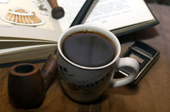 A cup of coffee with a pipe royalty free stock photos