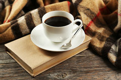 Cup of coffee with plaid and book on a grey wooden background Stock Image