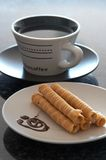 Cup of coffee and a plate of c. A white cup of coffee on black saucer. Next to it are baked swirls filled with cream and decorated with chocolate sauce. Shallow Royalty Free Stock Photos