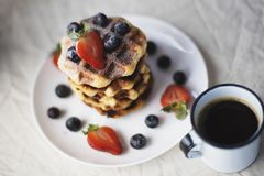 A cup of coffee and a plate of waffles and berries Stock Images
