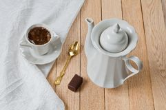 A cup of coffee on a plate of white porcelain set on a wooden ta Stock Photo