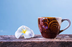 A cup of coffee and plumeria on wooden table with blue sky background Royalty Free Stock Photography