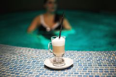 A cup of coffee in the pool and a girl stock photos