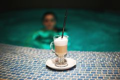 A cup of coffee in the pool and a girl royalty free stock photo