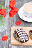 Cup of coffee with poppy buns glazed with chocolate and poppy fl Stock Photos
