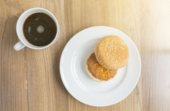Cup of coffee and pork burger on wooden table with sunlight Royalty Free Stock Images