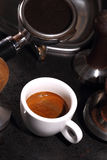 Cup of coffee and portafilter of an espresso machine Royalty Free Stock Photo