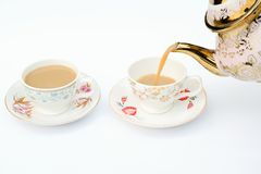 A cup of coffee with coffee pot is being poured into the cup. Stock Image