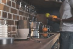 Cup and coffee pot on kitchen table Royalty Free Stock Image