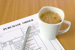 Cup of coffee on purchase order form Stock Photos