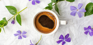 Cup of coffee and purple flowers on bed sheets Stock Images